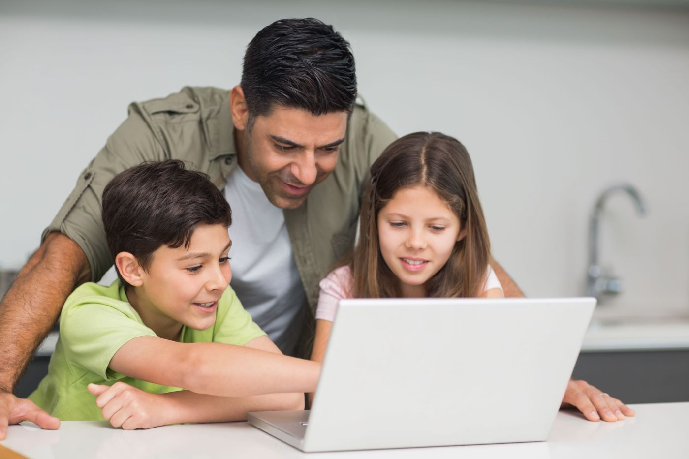 Father helps out his children with something on the laptop