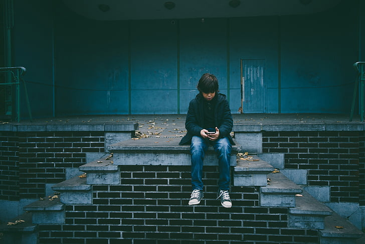 young boy sitting alone and watching something on his mobile phone