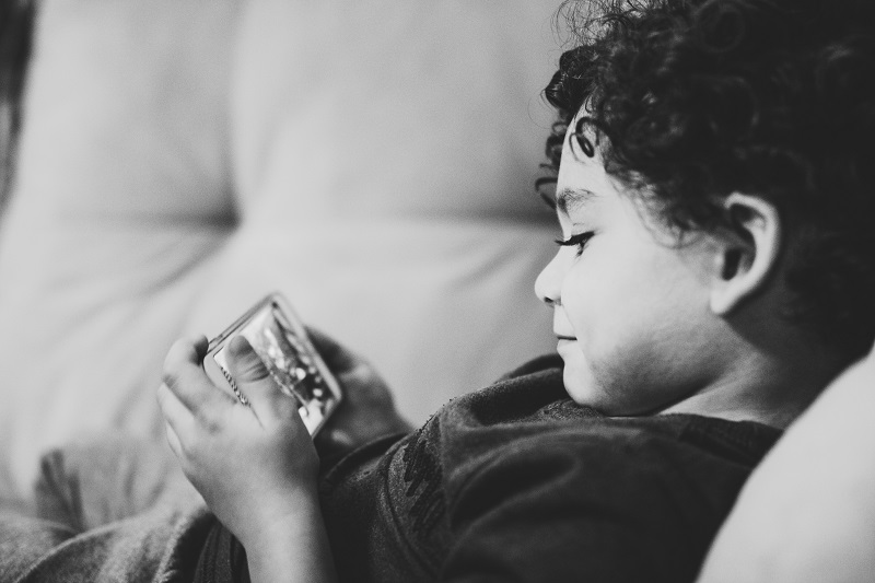 young boy lying on couch watching a video on a smartphone