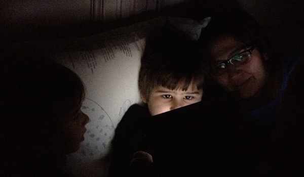 Kid using iPad in bed