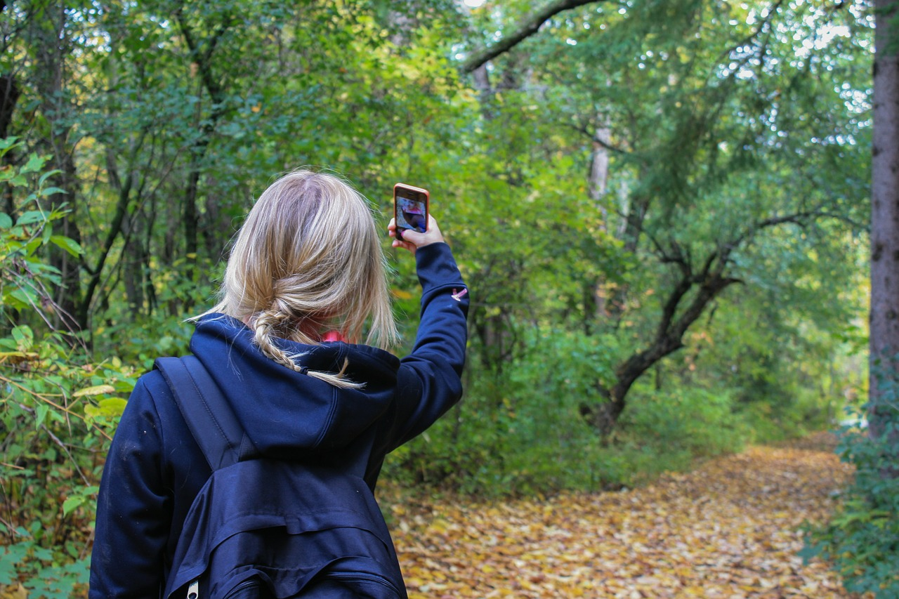 Teen walking in forest taking a snap for Instagram