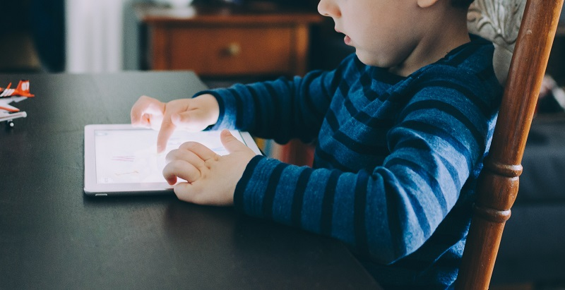 young boy playing on an iPad