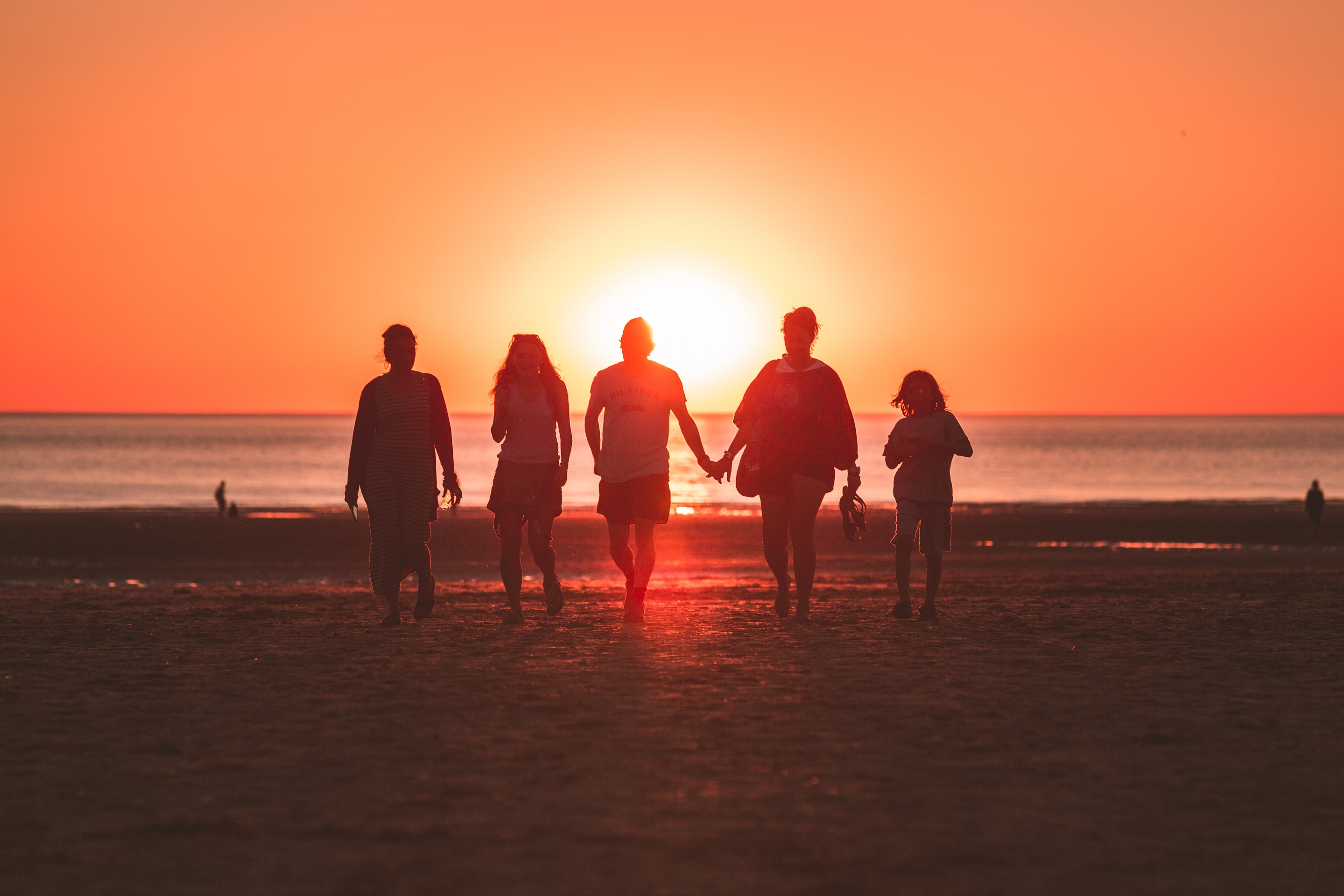 Family of 5 walking on the beach at sunset