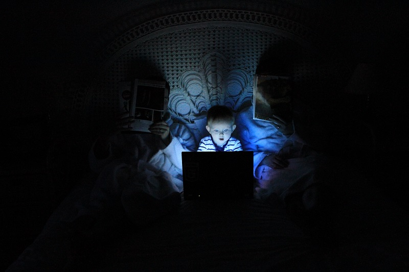 baby staring at laptop screen while lying between parents in bed