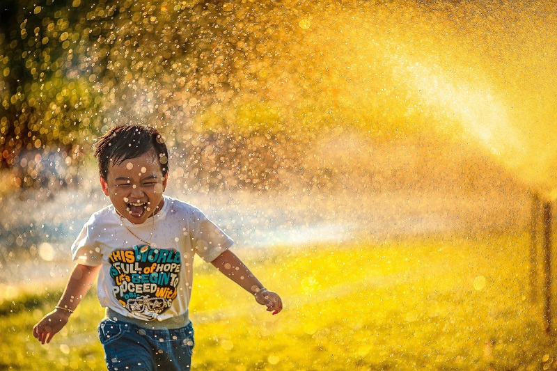 boy running through a water shower