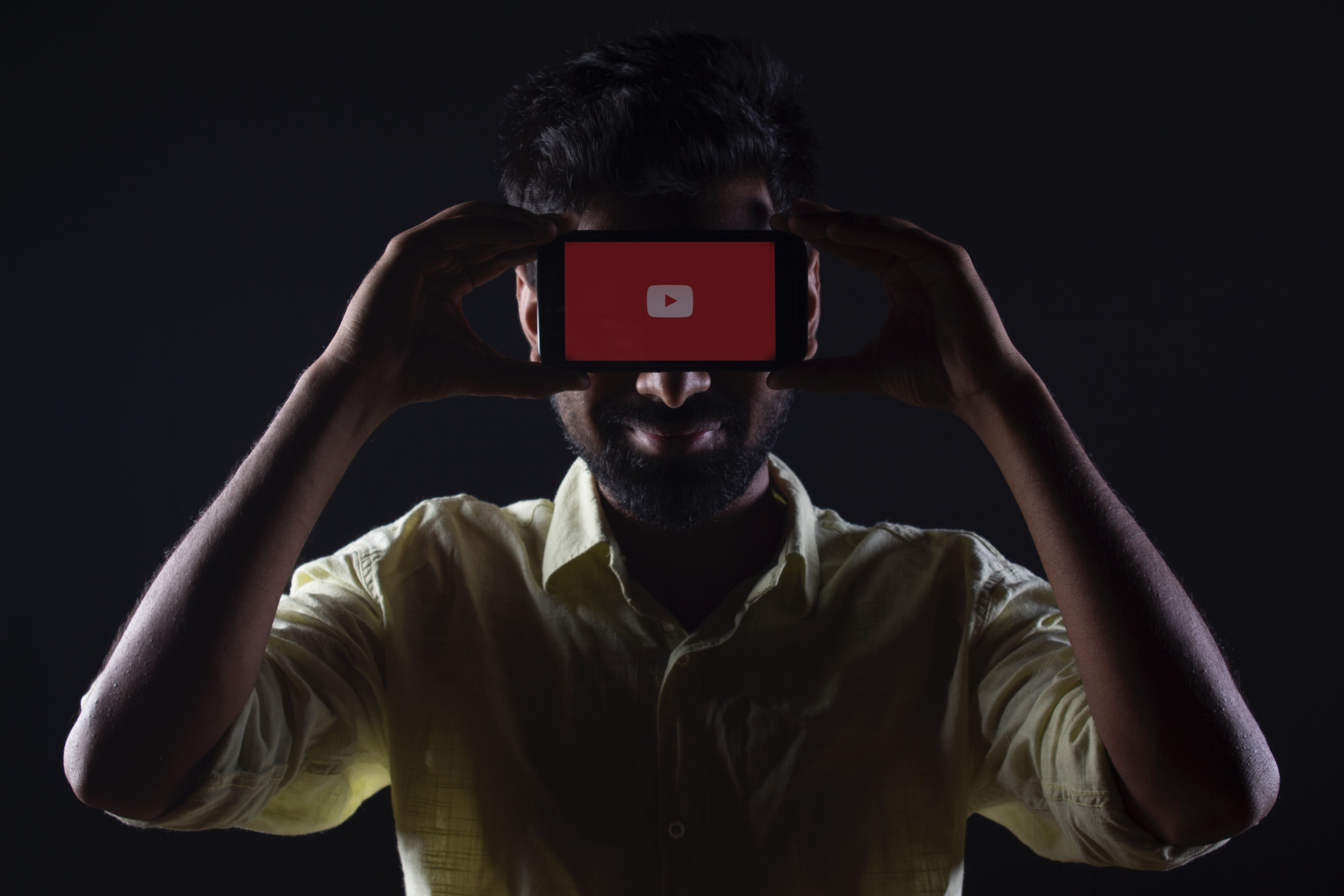 Man holding phone to eyes with YouTube logo displayed on screen
